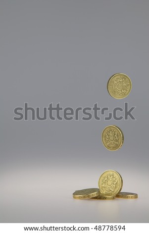 British One Pound Coins falling from above and landing in a pile - stock photo