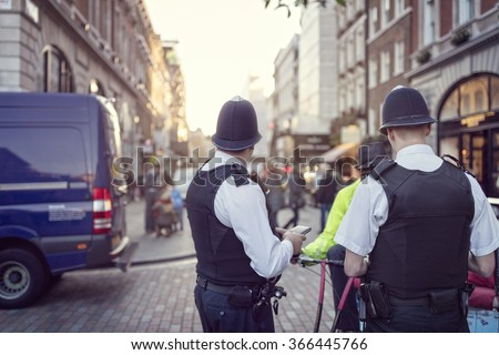 British police officers in helmets policing London streets - stock photo