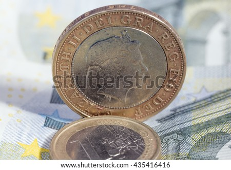 British pound coin and euro coin on euro banknote - stock photo