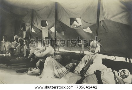 British POWs of the Dardanelles campaign in Turkish custody. Some are bandaged, as they occupy sleeping quarters in a tent. 1915-1916, during WW1