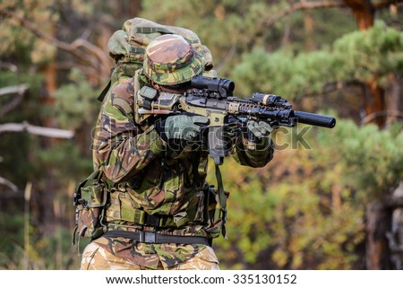 British soldier with military backpack aiming from his rifle in forest/Gunner aims in forest - stock photo