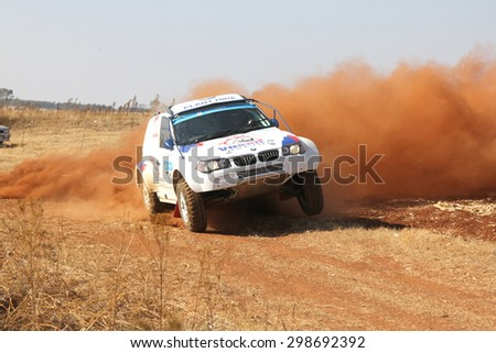 BRITS, SOUTH AFRICA - July 11:  Africa-Offroad Racing Rally,  on July 11, 2015 at Koster, North West Province, South Africa.  Drifting white BMW rally car kicking up dust on turn.  - stock photo