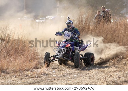 BRITS, SOUTH AFRICA - July 11:  Africa-Offroad Racing Rally,  on July 11, 2015 at Koster, North West Province, South Africa.  Quad Bike kicking up trail of dust on sand track during rally race. - stock photo