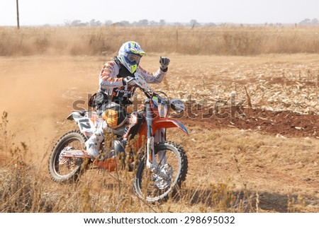 BRITS, SOUTH AFRICA - July 11:  Africa-Offroad Racing Rally,  on July 11, 2015 at Koster, North West Province, South Africa.  Motorbiker thumbs up kicking up trail of dust. - stock photo