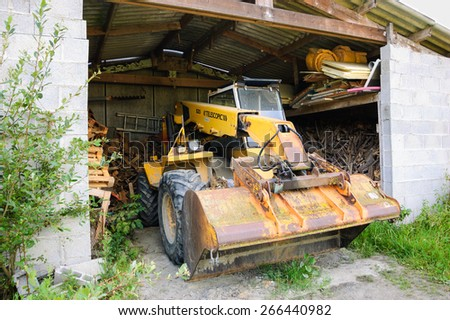 BRITTANY, FRANCE - JULY 17, 2014: Old yellow tractor with telescopic loader in the barn.  Telescopic handlers are widely used in agriculture and industry.