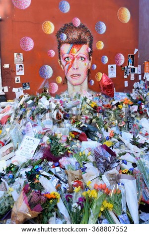 BRIXTON, LONDON, UNITED KINGDOM- January 28, 2016: Flowers left beneath a mural as fans paying tribute to David Bowie in his birthplace. Bowie was born as David Robert Jones in Brixton, London, UK. - stock photo