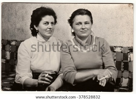 BRNO, THE CZECHOSLOVAK SOCIALIST REPUBLIC - CIRCA 1960s: Vintage photo shows women smoke cigarettes and they sit on the sofa