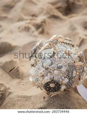 Broach bridal bouquet laying in the sand
