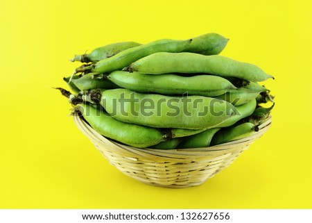 broad bean pods and beans on yellow background . - stock photo