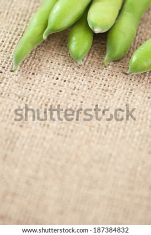 broad bean pods on jute background  - stock photo
