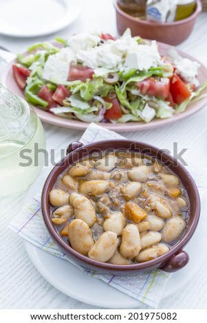 Broad beans in a bowl and greek sald, Greece - stock photo