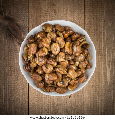 Broad beans in a white bowl  on wooden boards top view - stock photo