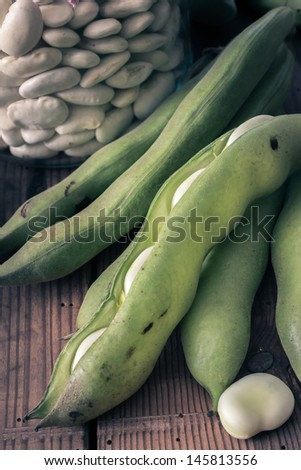 Broad Beans on a wooden Table with Jar, full of dry beans - stock photo