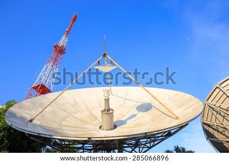 Broadcast TV antenna and satellite dish signal on blue sky background - stock photo