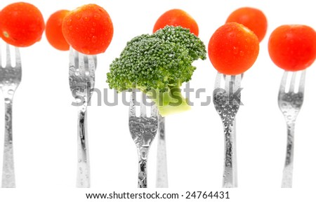 Broccoli and tomatoes on forks over white.