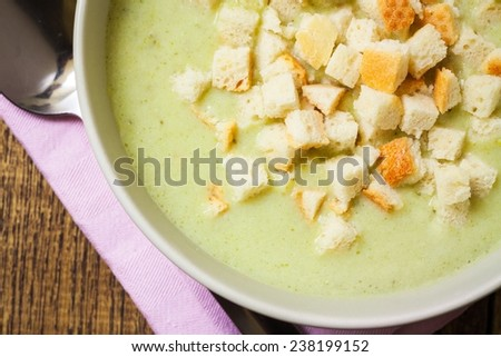 Broccoli cream soup and dried crusts, top view and closeup - stock photo