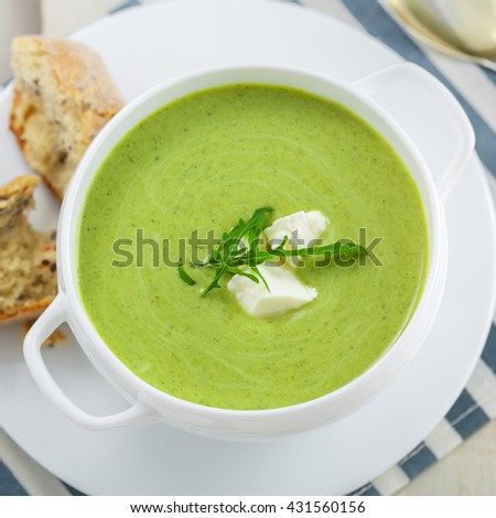 Broccoli cream soup with bread on a table. Classic European food. Top view. Close-up shot. - stock photo