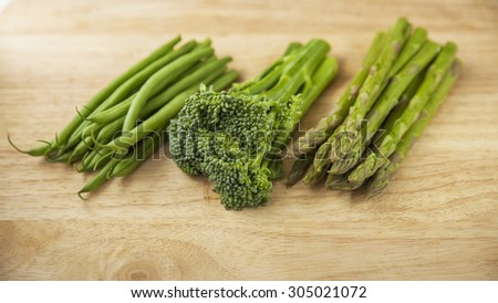 broccoli fine beans and asparagus on wooden chopping board - stock photo