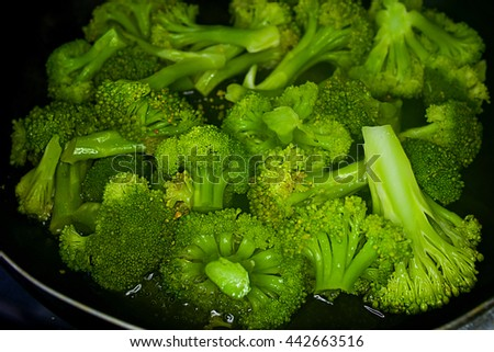broccoli frying in a pan with cream sauce