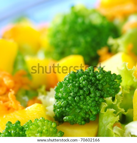 Broccoli on fresh salad (broccoli, mango, carrot, lettuce) in a bowl with blue background (Very Shallow Depth of Field, Focus on the front of the broccoli) - stock photo
