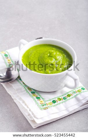 Broccoli soup in a bowl over grey background