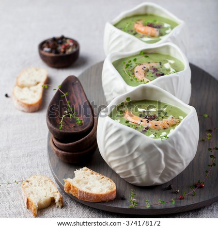 Broccoli, spinach cream soup with shrimp in a white bowls on a wooden board - stock photo