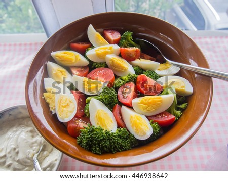 Broccoli tomato egg salad in wooden bowl on party table.