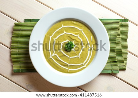 Broccoli vegetable soup cream in white plate on green and white background - stock photo