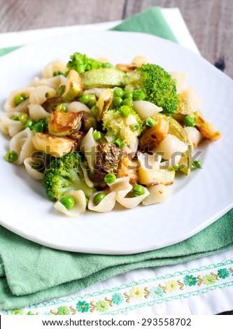 Broccoli, zucchini and pea pasta shell on plate - stock photo