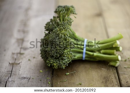 Broccolini on a rustic wooden surface. - stock photo