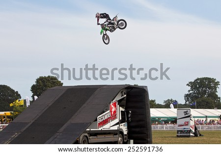 BROCKENHURST, UK - JULY 31: A Squibb FMX team rider completes his stunt jump for the public and makes a successful landing onto the ramp at the New Forest Show on July 31, 2014 in Brockenhurst - stock photo