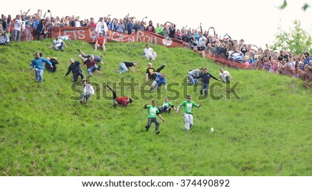 BROCKWORTH, UK - MAY 25, 2015: Revellers take part in the traditional cheese rolling races on Cooper's Hill. Thousands attended the unofficial annual event which dates back to at least 19th century. - stock photo