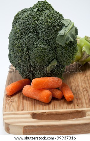 brocolli and carrots on the cutting board on the white background - stock photo