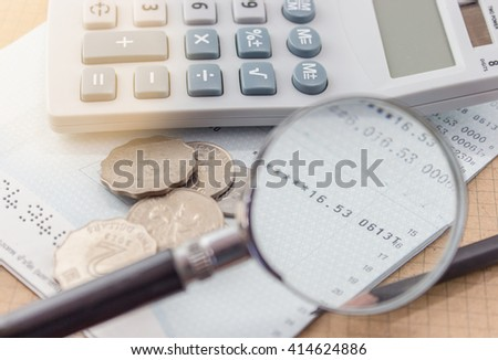 Broke concept, Account balance is running low : coins, calculator pencil and passbook. Magnifying at current balance. - stock photo