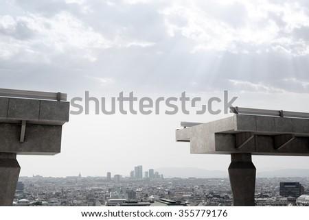 Brokeen bridge with gap above city scape - stock photo