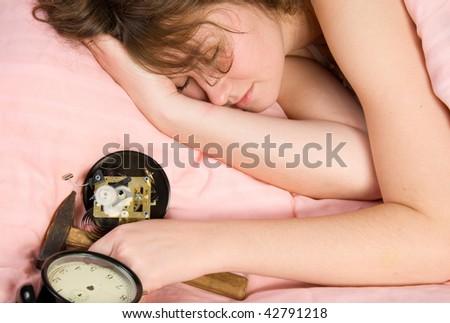 broken alarm clock and sleeping woman - stock photo