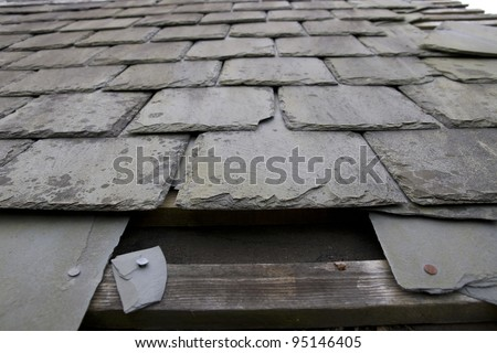 broken and fallen slate leaves hole in a roof due to storm or decay - stock photo
