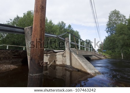 Broken asphalt near a bridge, natural disaster caused by heavy rain - stock photo