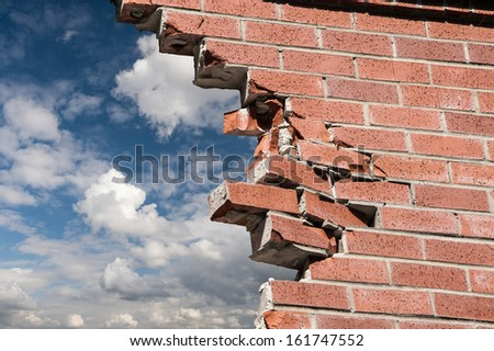 Broken brick wall and blue sky with clouds. - stock photo