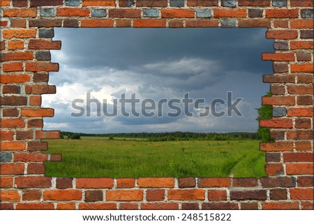 broken brick wall and view to field with dark thunder storm clouds - stock photo
