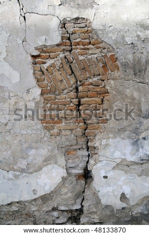 Broken brick wall which has darkened from time