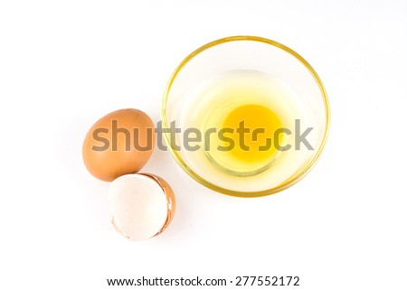 Broken brown egg in bowl on a white background.