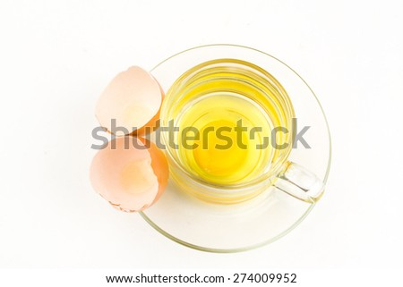 Broken brown egg in cup on a white background. - stock photo