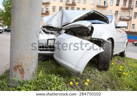 Broken bumper and hood of vehicle as a result of a collision with a pole, close-up. The accident at the crossroads - stock photo