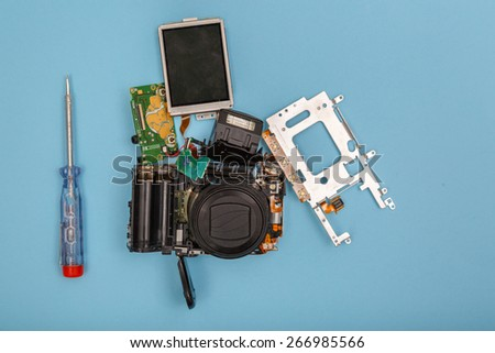 Broken camera on cyan background with copy space - stock photo