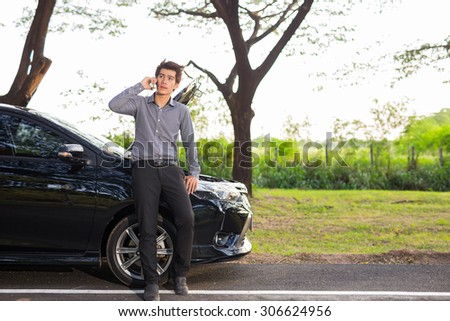 Broken car,Young businessmen talking on a cell phone by a broken car On Country Road Phoning For Help - stock photo