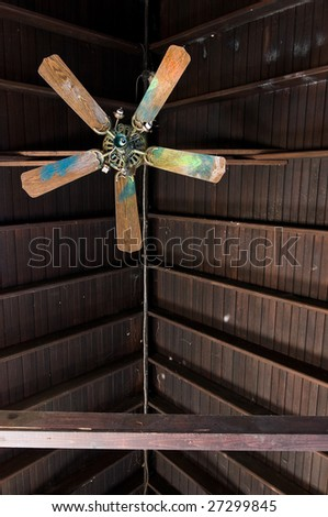 Broken ceiling fan in abandoned building, shot straight up towards the exposed wood roof - stock photo