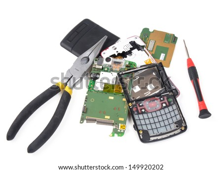 Broken cell phone in pieces with tools - stock photo