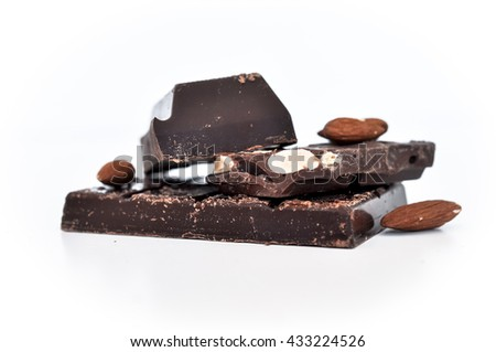 Broken chocolate bar and almonds, isolated on white background
