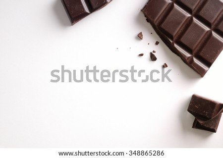 Broken chocolate bar isolated on white table. Horizontal composition. Top view - stock photo